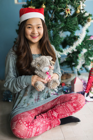 a67770c99a9 Asian Chinese happy woman with santa claus hat hold teddy bear doll near  Xmas tree.