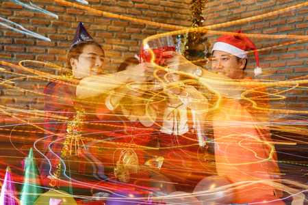 Group of young Asian friends toasting glasses of red wine  for Christmas or xmas celebrating party. photo with light trail technique effect for ceremony holiday celebration.
