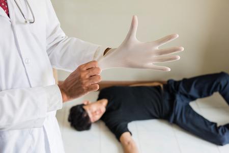 El médico forense usa guantes de goma antes de realizar la autopsia o la autopsia de un hombre muerto por sobredosis. Adicción a las drogas y problema social para adolescentes, estudiantes y trabajadores. Foto de archivo