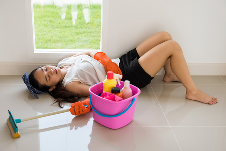 Tired or exhausted Asian female owner sleep in new house after cleansing home at first day to start new life.