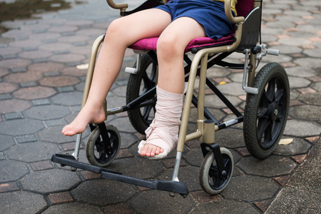 Patient boy sitting on wheelchair to give a walk and refreshment in park. Closeup Broken leg by accident wrapped with plaster cast and occlusal splint. Health kid insurance with copy space for text. Reklamní fotografie - 119973707