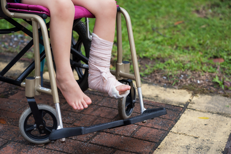 Patient boy sitting on wheelchair to give a walk and refreshment in park. Closeup Broken leg by accident wrapped with plaster cast and occlusion splint. Health insurance for children with copy space. Banco de Imagens