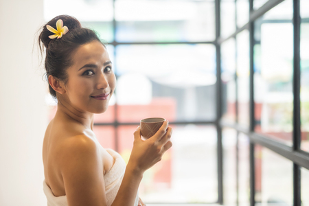Portrait of happy Asian woman in white towel or bathrobe hold cup of hot green tea in spa after body care treatment by having Thai massage with copy space for text.