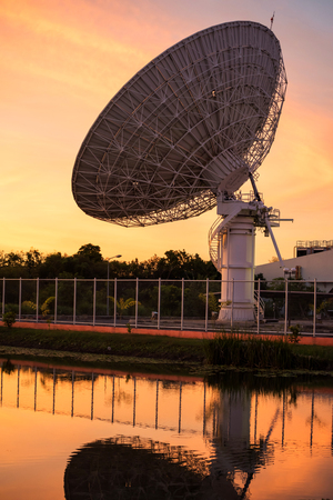 Big satelite dish or antenna with skyline reflection on water pond against twilight sky at sunset. Telecommunication Technology concept.