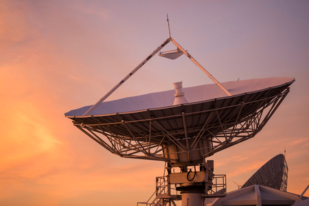 Big satelite dish or antenna against twilight sky at sunset. Telecommunication Technology concept.