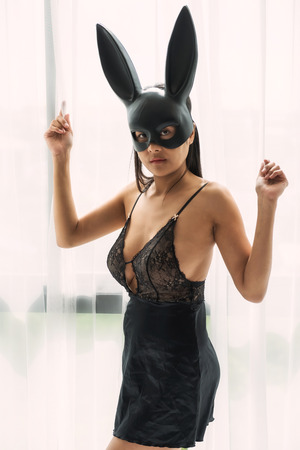Portrait of attractive Asian woman with black rabbit bunny ear mask and black See Through Sleepwear Suit Lingerie at white curtain. Easter and halloween fancy fashion dress up for party.