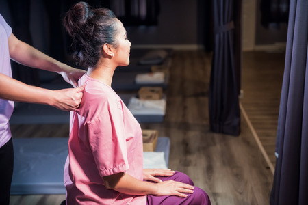 Portrait of Asian beautiful woman relax in spa. Body care treatment by Thai massage. Cute girl with traditional dress massaging back and backbone by professional massaged female hands.