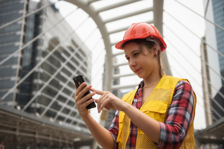 Young American female engineer with orange helmet using smartphone or mobile phone to check construction project plan ordered by construction site manager in Bangkok city. Industrial concept Imagens