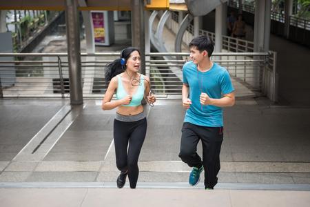 Glückliches asiatisches Paar, das oben am modernen Stadtskywalk läuft. Aktive Lifestyle-Sportler, die Cardio-Klettertreppen trainieren, während sie Online-Musik vom Smartphone in der Stadt hören. Standard-Bild