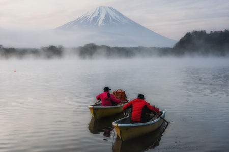 Fishermen saling boat for fishing at Lake Shoji in the morning with heavy mist and mount fuji or fujisan background, Japan. Leisure and travel destination.