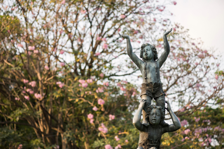 Children monument or statue against blur pink flowers on tree at Vachirabenjatas park or  Rot Fai garden, Bangkok, Thailand