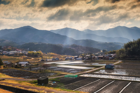 landscape of local houses and rice farm surround by mountain with rays light near Magome juku, Kiso valley, Nakatsugawa, Gifu Prefecture, Japan.