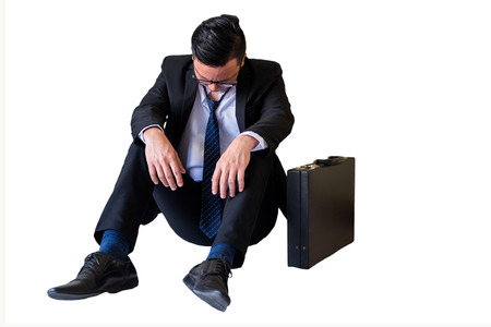 Depressed young Asian businessman with glasses give up and sit on floor isolated on white background. Feeling sad and headache after getting lay off or fired in office.