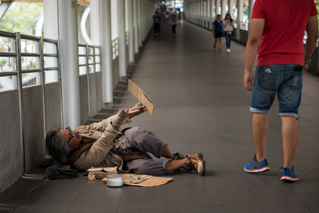 Smell homeless dirty old guy beg for money to young tourist man in urban city skywalk. Poverty and social issue concept. Give and share with sympathy.