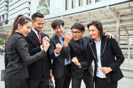 International Business colleague celebrate success with arms raised in modern city after project achievement. Businessman group in suits complete fintech deal. Banco de Imagens