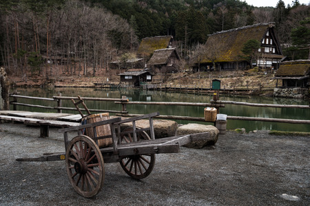 Old wooden handbarrow in front of sloped-roof and thatched-roof houses at Hida Folk Village, Takayama, Japan. Here is famous of similarity preserved village as Shirakawago. Banco de Imagens