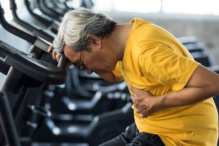 Senior man suffering from chest pain while exercising on biking machine in fitness gym. Old male guy heart attack. Elderly accident from sport training. Healthy lifestyle concept.