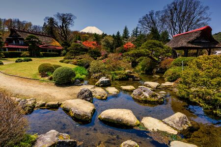 Traditional heritage house with spring garden and mountain Fujisan or Fuji view from Oshino Hakkai, Yamanashi, Japan. Famous travel destination between Lake Kawaguchiko and Yamanakako.