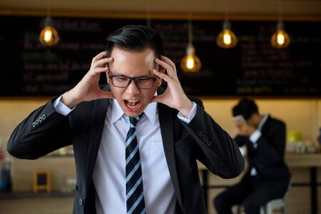 Angry Asian businessman manager shout loudly and feel headache. Employee is stressed and put hands to cover his head in coffee shop.