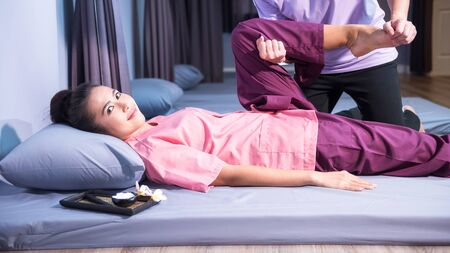 Portrait of Asian beautiful happy woman relax by Thai massage. Foot, calf, and leg massaging treatment with aroma lotion in spa salon by professional. Health care industry concept. Stock Photo - 128218518