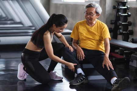 Old man relaxing after getting massage by beautiful Asian women after exercise or work out foot and legs at fitness gym with copy space for text. Happy healthy lifestyle for elderly guy, age over 60.