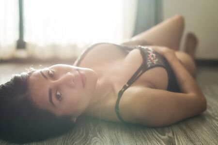 beautiful tan Asian woman with sexy black bra lying on wooden flloor near windows with flare natural light. Portrait of brunette girl with natural big boobs. Sex appeal.