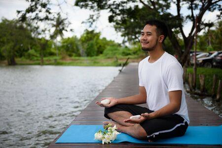 Hübscher indischer Mann mit Bart führt Yoga-Handmeditationsübung mit weißem Felsen an der Holzbrücke in der Nähe des Teiches durch. Gesundheits-Lifestyle- und Fitness-Konzept Standard-Bild