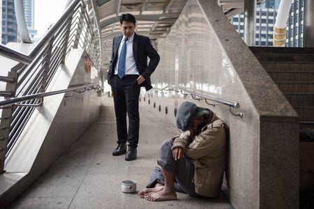 Hombre de negocios de piedad con traje negro mira mendigo mayor o viejo vagabundo en paseo por la ciudad en la ciudad urbana. Concepto de pobreza y problema social. Dar y compartir con simpatía.