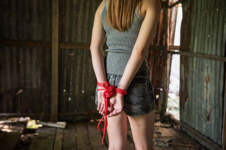 Hostage girl hands tied by red rope in abandon house. Victim woman kidnapping concept from terrorist. Sexual abuse or rape in dirty room with copy space for text.