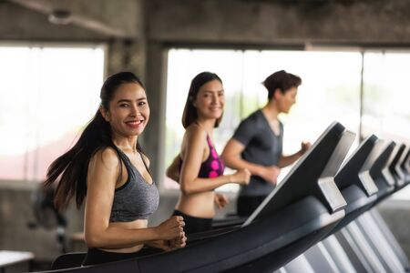 Group of young Asian female and male friends running on treadmills in sport fitness gym. two women and man run on machine. workout, exercise, training healthy lifestyle. Stockfoto
