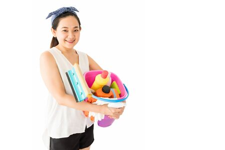 Beautiful Asian smile housewife woman or housekeeper hold home cleansing equipment in pink bucket isolated on white background. Happy girl ready for cleaning. Home hygiene with copy space for text. Imagens