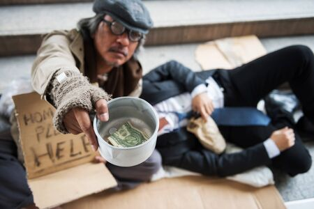 Old beggar or homeless senior guy raise donated bowl with dollar bill to ask for money while drunk Buinessman holding beer bottle and sleeping on him at urban city. Social issue