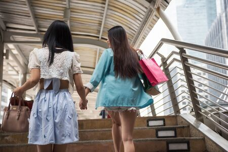 Rear shot of happy women friends walking upstair to shopping in city. Two beautiful young Asian girls shop in modern Bangkok town. Portrait of smile girls carry many shopping bags.