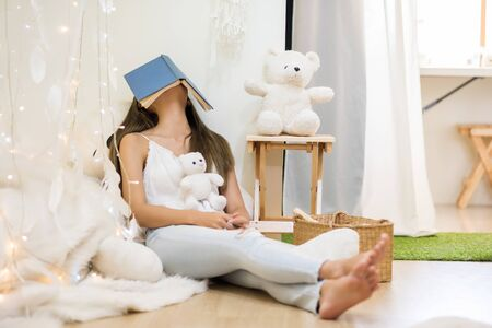 Beautiful Asian tired female student take a nap or sleep with book cover her face after hard reading for final exam. woman rest near bear doll in home living room.