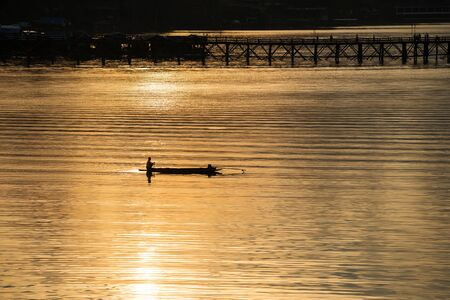 Silhouette pescatore in barca per la pesca all'alba con ponte in legno Mon e riflesso del sole sul fiume Songkalia, Sangkhlaburi, Kanchanaburi, Thailandia. Famoso punto di riferimento della destinazione di viaggio in tailandese.