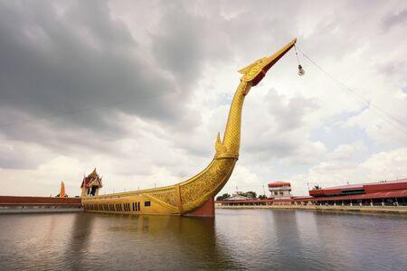 Big golden Suphan Hong boat or supannahong in large pond at Wat Sra Long-Ruea or Sra Long Rua in Kanchanaburi, Thailand. Famous travel destination for Buddhist religion.