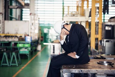 Stressed Factory manager or businessman owner sit on machine with factory background. Depress express feeling for bankruptcy, unemployed, or fired. Unsuccessful industry concept.