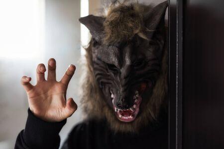 Frau oder Mann mit gruseliger Wolfsmaske und schwarzem Kostüm im dunklen Raum mit Randlicht aus dem Fenster. 2019 Halloween Süßes oder Saures Konzept mit Kopienraum für Text.