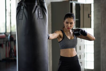 Asian Female boxer punch punching bag at fitness gym. Athletic Strong girl training Thai boxing for bodybuilding and healthy lifestyle concept. Happy woman workout in sport club. Stockfoto