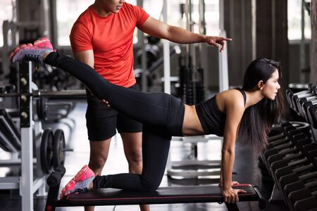 Portrait of personal trainer help stretching leg to beauty Asian tan woman in fitness sport gym. Sexy girl working out on chair for bodybuilding and healthy lifestyle.