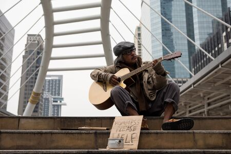 Old beggar or Homeless dirty man artist sing and play guitar music on stair of modern city with donate bowl, paper cardboard with help text to ask for donation. Poverty in town