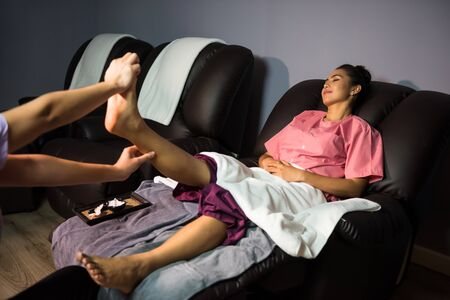 Foot and leg Thai massage on aroma sofa bed to beautiful Asian tan woman in spa salon.  Health care and Relax to heal pain concept. Medical Practitioners or traditional doctor.
