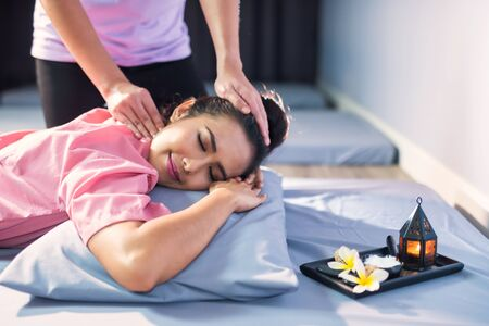 Asian beautiful woman relax in spa. Body care treatment by Thai massage with lotion, candle, Plumeria on bed. Health care to heal pain concept. Alternative medical Practitioners or traditional doctor