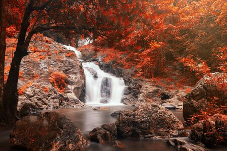 Cascade Motion Wasserfall im Herbst des Sarika Nationalparks, Nakhon Nayok, Thailand. Herbstrotes Laubblatt durch Farbverfahren. Naturzusammenfassung und Hintergrund durch lange Belichtung des großen Stoppers. Standard-Bild