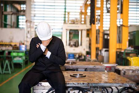 Échec Le directeur d'usine ou le propriétaire d'un homme d'affaires s'assoient et pleurent sur une machine avec un arrière-plan d'usine. Déprimez le sentiment d'être en faillite, au chômage ou licencié. Concept d'industrie infructueux.