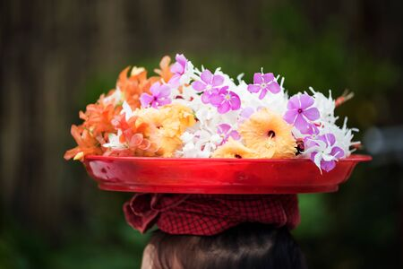 Mon girl or woman carries flowers on red tray on head with blurred bokeh foliage background in Sangkhlaburi, Kanchanaburi, Thailand. Archivio Fotografico