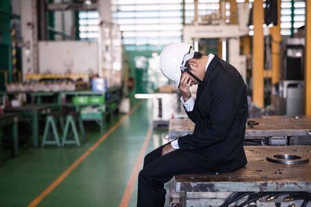 Un directeur d'usine stressé ou un propriétaire d'homme d'affaires s'assoit et pleure sur une machine avec un arrière-plan d'usine. Triste sentiment express de faillite, de chômage ou de licenciement. Concept d'industrie infructueux.