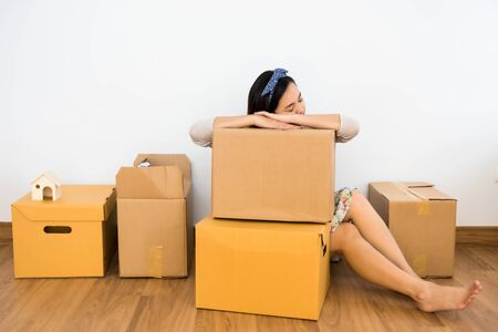 Tired Asian woman sleep on cardboard carton box after moving to new house. Wife move to new empty home to start family life. Architecture and Real estate industry. Stok Fotoğraf - 137897308