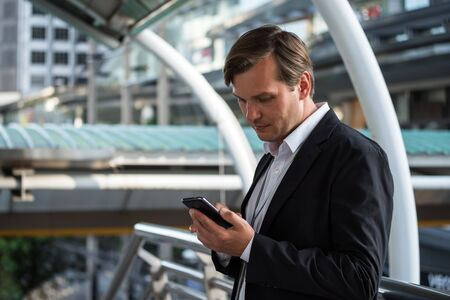 American professional businessman using smart phone. Middle-aged manager holding mobile smartphone using app texting outside office buildings. Reklamní fotografie - 138201717