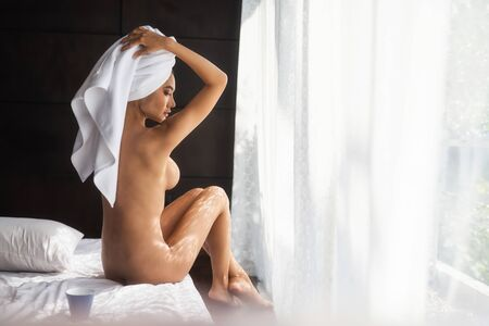 Beautiful young Asian woman wrapped shower towel after taking a bath sit naked on bed near window curtain. Sexy nude tan girl relax after taking a bath.
